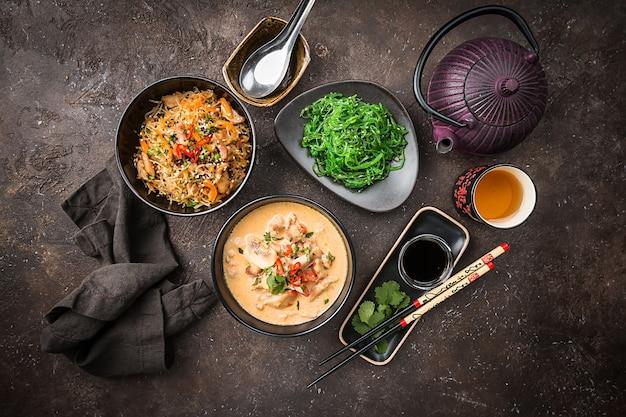 アジア料理、タイ料理。トムカーガイのスープ、パッタイヌードル、グリーンサラダ、ソース、緑茶。上面図