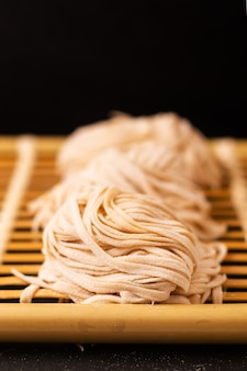 Asian food homemade oriental egg noodles on bamboo tray