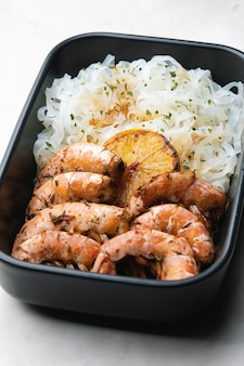 Азиатская кухня: рисовая лапша с креветками и зеленью в миске. соевый соус с чесноком, имбирем и лимоном.