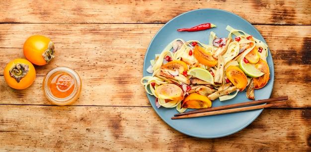 アジア料理、麺、柿、なすのサラダ。