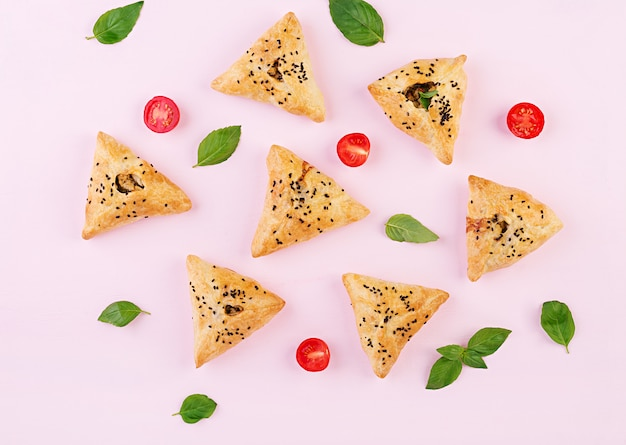 Asian food, samsa (samosa) with chicken fillet and green herbs on pink, top view
