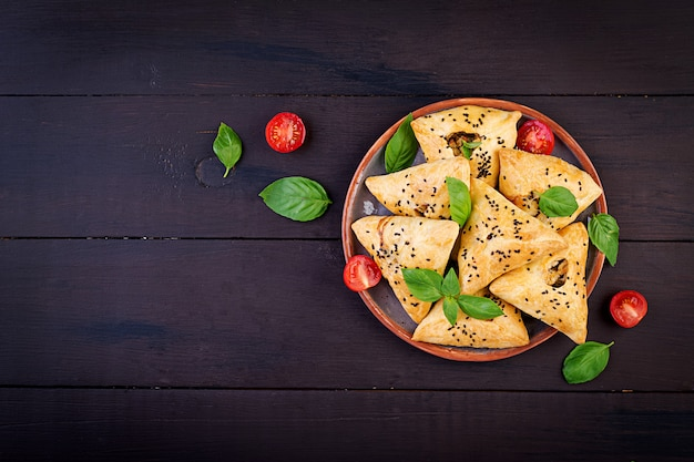 Asian food, samsa (samosa) with chicken fillet and green herbs on wooden, top view