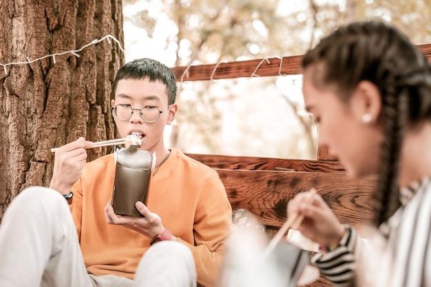 アジア料理。真面目なブルネットの男性が深く考えながら木に寄りかかって Premium写真