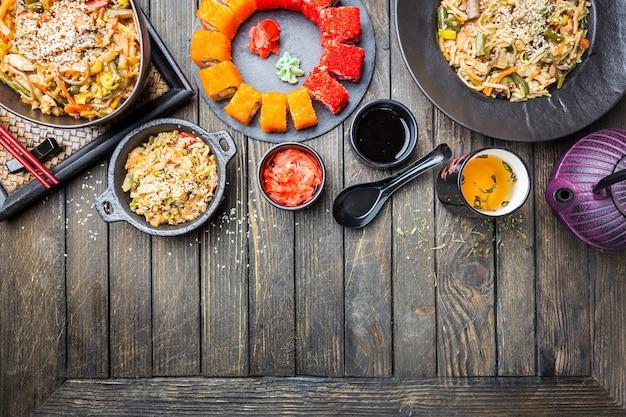 Набор азиатских блюд служил на черном деревянном. китайская, японская и вьетнамская кухня, суши, рис и лапша.