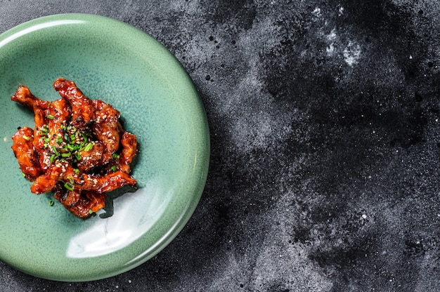 Asian food: spicy pork in sweet and sour sauce. black background. top view. copy space