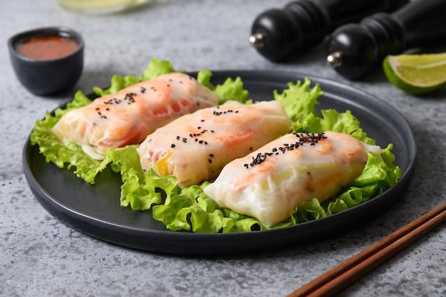 エビ、灰色の背景にライスペーパーで包まれた野菜とアジア料理の春巻き。閉じる。ベトナム料理。
