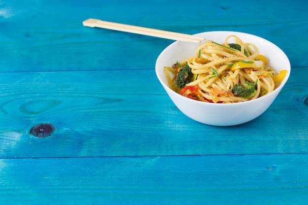 Asian food. stir fry udon noodles with vegetables on a withe plate, blue wooden backgound, cooked in wok, copy space