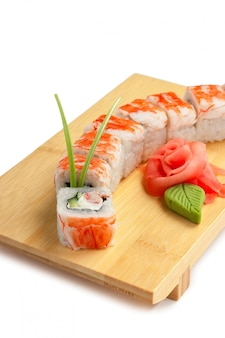 白い表面に分離された木製のプレートにアジア料理寿司
