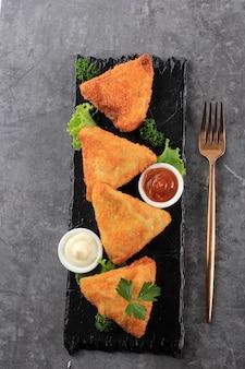 アジア料理。トマトソースとマヨネーズの三角形のベジタリアンサムサ(サモサ)。 risolessayurとしてインドネシアで人気があります。ダークグレーセメント背景コピースペース上面図