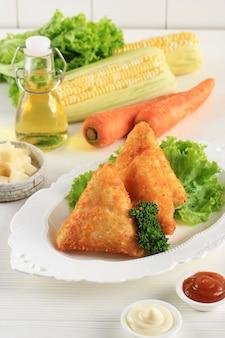 アジア料理。トマトソースとマヨネーズの三角形のベジタリアンサムサ(サモサ)。 risolessayurとしてインドネシアで人気があります。白いプレート、白いきれいな背景。