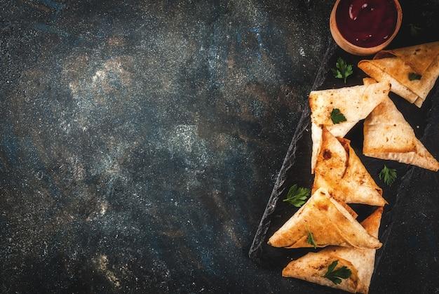 Asian food. vegetarian samsa samosas with tomato sauce. dark blue   top view