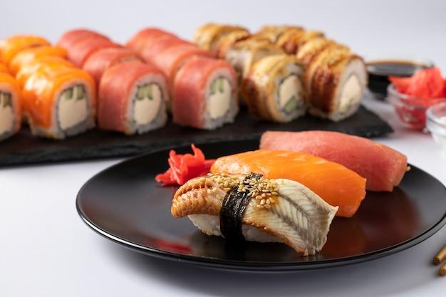 白い表面の黒いプレートにフィラデルフィアチーズとサーモン、マグロ、ウナギの寿司セットを使ったアジア料理