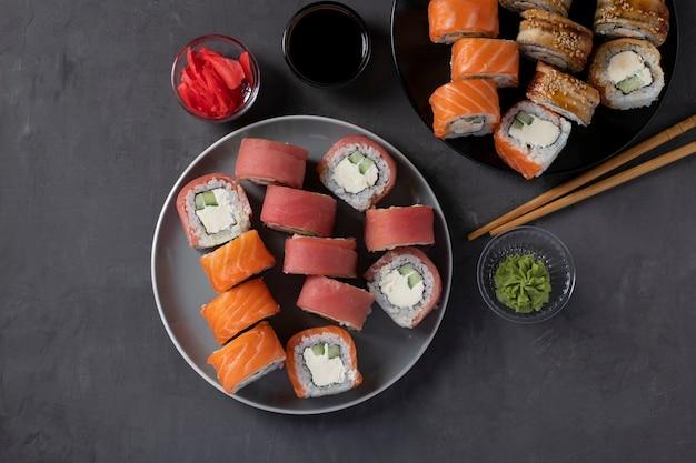 Азиатская еда с набором суши из лосося, тунца и угря с сыром филадельфия на двух тарелках на сером фоне. подается с соевым соусом, васаби, маринованным имбирем и палочками для суши. вид сверху