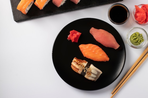 Asian food with sushi set of salmon, tuna and eel with philadelphia cheese on black plate on a white surface. served with soy sauce, wasabi, pickled ginger and sticks for sushi. top view