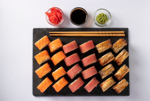 Asian food with sushi set of salmon, tuna and eel with philadelphia cheese on on a slate board on a white surface