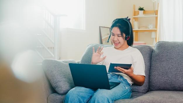 社会的距離が家にいて、自己検疫時間にいるとき、自宅のリビングルームの職場で顧客とラップトップ作業呼び出しのビデオ会議を使用してアジアのフリーランスのビジネス女性カジュアルウェア。