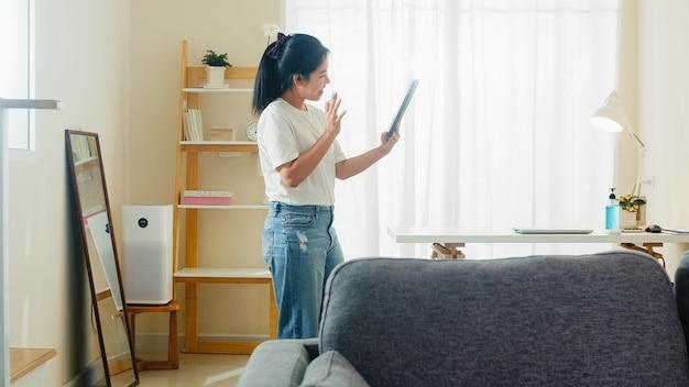 Носка азиатской независимой бизнес-леди вскользь используя видео-конференцию звонка таблетки работая с клиентом в рабочем месте в живущей комнате от дома когда социальное дистанцирующ пребывание дома и время карантина собственной личности.
