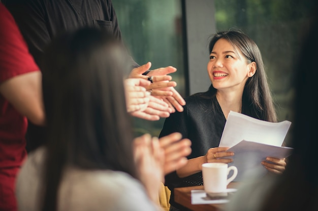 Азиатская внештатная команда встречает счастье в современном домашнем офисе