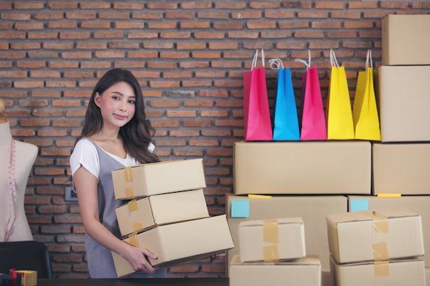 アジアのフリーランスの女性売り手は、自宅でパッケージングプロセスのために製品を準備します。オンライン販売