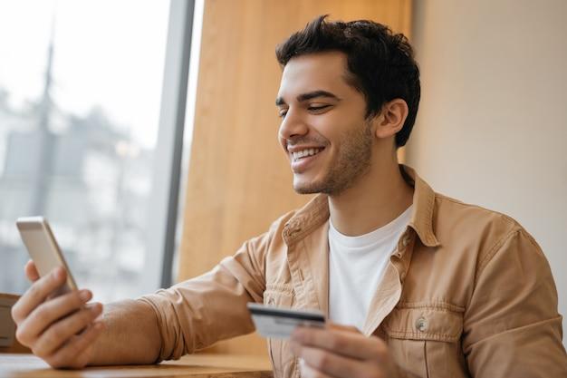 Азиатский фрилансер, держащий кредитную карту с помощью мобильного телефона, получает оплату