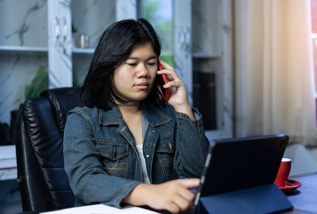 Asian freelancer using tablet working video conference with a customer in home office. marketing and financial. deal with customers by online apps. online selling and receiving order. work from home.
