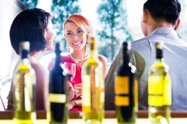 Asian friends drinking wine in fancy bar