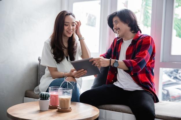 Азиатские друзья любят использовать планшет и разговаривать с партнером