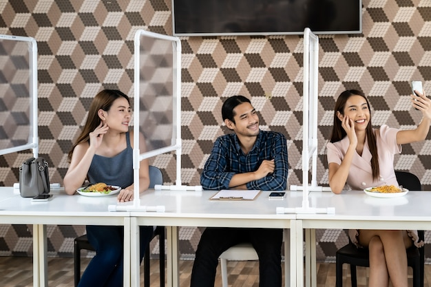 Asian friends take selfie in social distancing restaurant