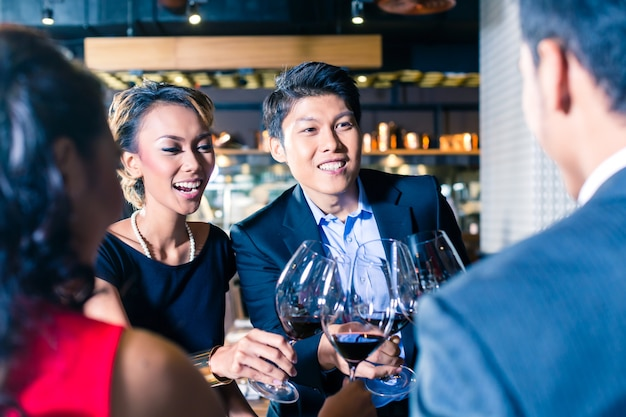 Asian friends toasting with red wine in bar