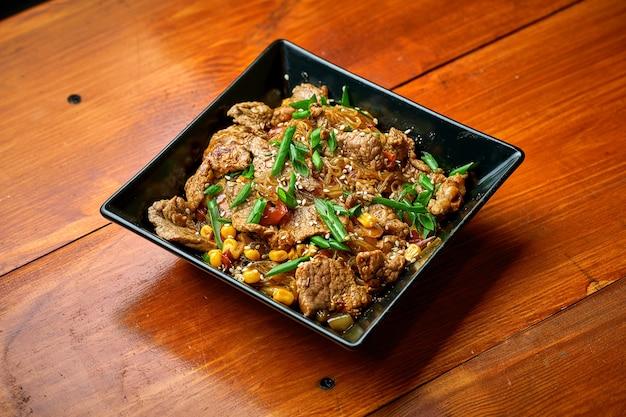 Азиатская лапша фунчоза с говядиной, овощами и кисло-сладким соусом. целлофановая лапша вок