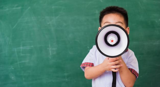 Asian funny cute little child boy kindergarten in student uniform speaking through megaphone against on green blackboard