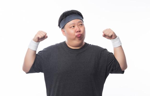 Азиатский смешной толстый человек в спортивной одежде, показывающий силу