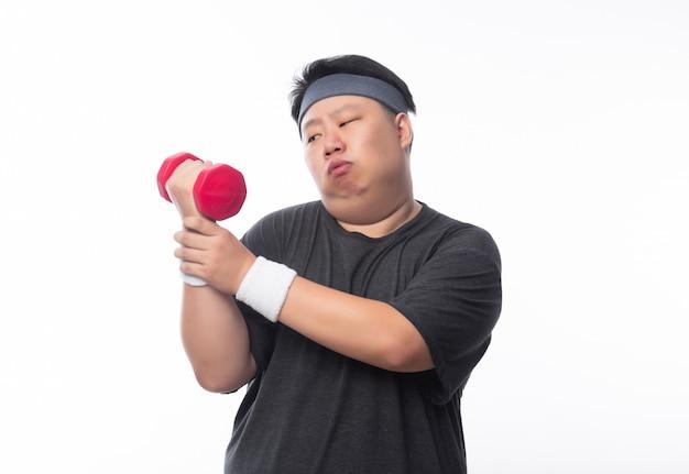 Азиатский смешной толстый человек в спортивной одежде устал работать с гантелями на белом фоне