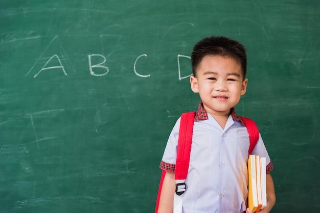 ランドセルを持つ学生服の幼稚園からのアジアの面白い小さな子供の男の子は本の笑顔を保持します