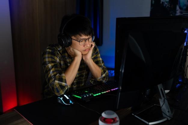夜に彼のコンピューターで遊ぶアジアのゲーマー