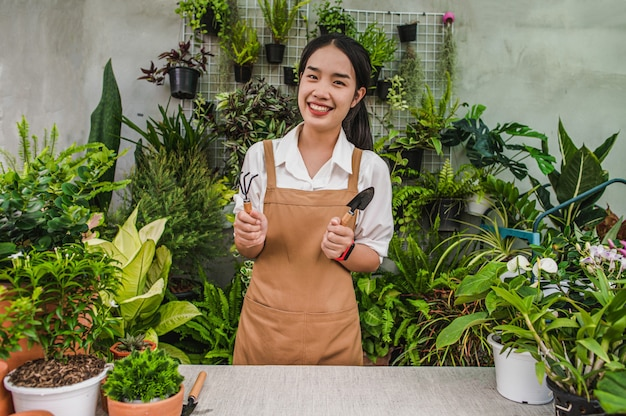 Asian gardener woman wearing apron stand and showing a shovel and pitchfork, equipment to transplants indoor plants and take care of plants at home