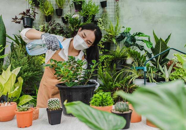 手に緑の観葉植物に水をまくためにスプレーを保持しているフェイスマスクとエプロンを身に着けているアジアの庭師の女性