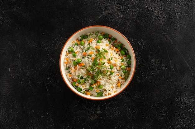 黒い石のテーブルの上の丸いプレートにアジアの付け合わせ、野菜、エンドウ豆、ニンジン、ネギを添えたご飯。