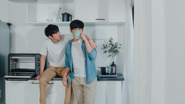 アジアの同性愛者のカップルがコーヒーを飲んで、家で楽しい時間を過ごします。幸せなリラックスした話を話している若いハンサムなlgbtq +男性は一緒に朝の家でモダンなキッチンでロマンチックな時間を過ごします。