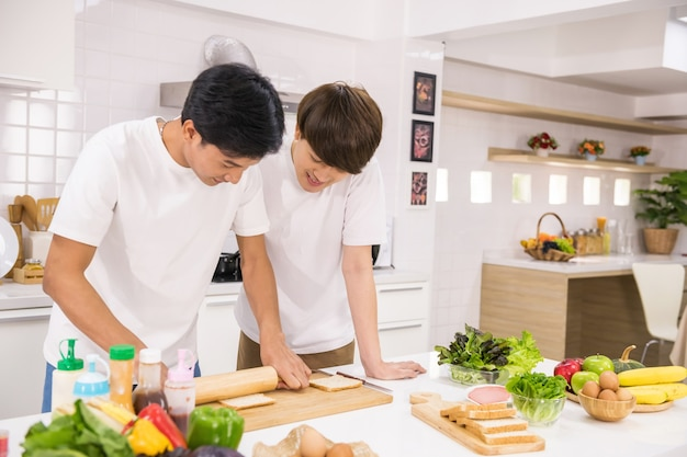 Asian gay couple grind wholewheat bread to make sandwich and salad at kitchen. happy young lgbt life at home. homosexual same sex family with healthy eat lifestyle in morning after wake up.