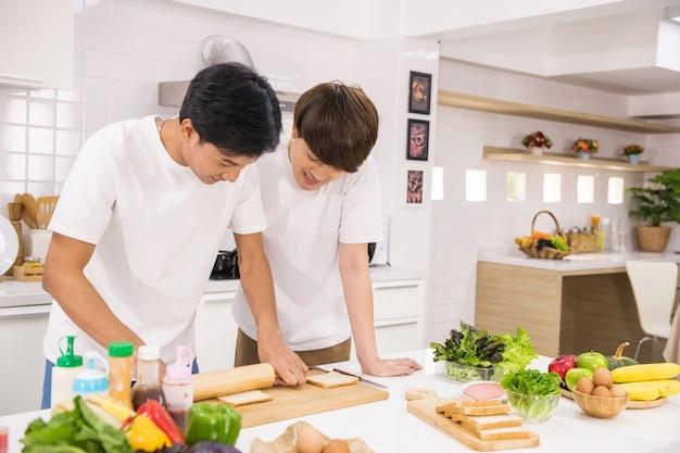 Азиатская гей-пара измельчает цельнозерновой хлеб, чтобы сделать бутерброд и салат на кухне. счастливая жизнь молодых лгбт дома. гомосексуальная однополая семья со здоровым питанием утром после пробуждения.