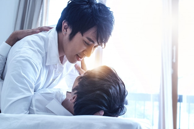 Asian gay couple kissing, homosexual couple on bed in bedroom