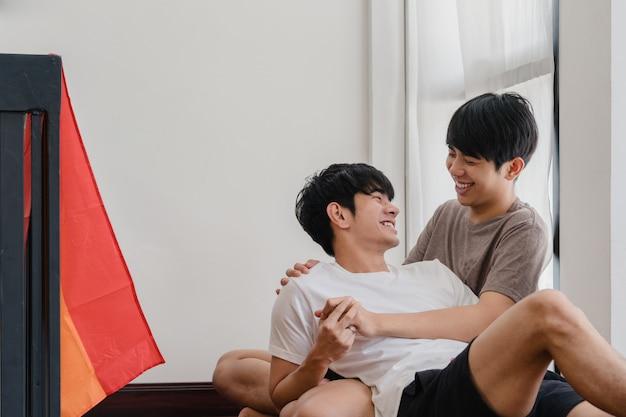 Азиатские пары гомосексуалиста лежа и обнимая на поле дома. молодые азиатские лгбт + мужчины, целующиеся счастливым, расслабляются, отдыхают вместе, проводят романтическое время в гостиной с радужным флагом в современном доме по утрам.