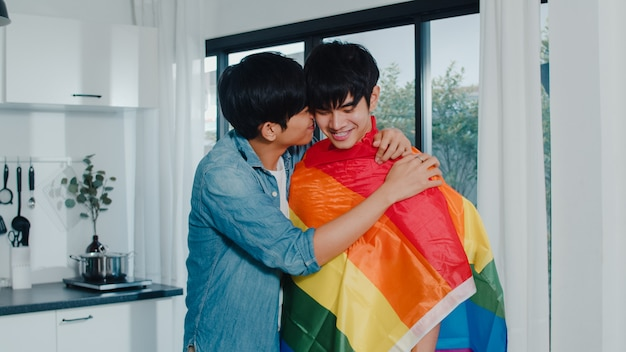 Asian gay couple standing and hugging room at home. young handsome lgbtq+ men kissing happy relax rest together spend romantic time in modern kitchen with rainbow flag at house in the morning .