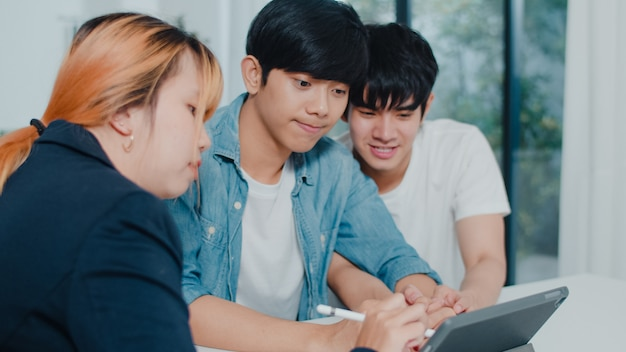 Asian gay lgbtq men couple sign contract on tablet at home, young couple consulting with real estate financial advisor, buying new house and handshaking with broker in living room at house .