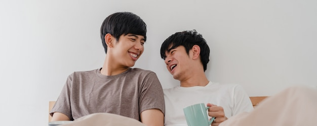 現代の家で素晴らしい時間を過ごして話しているアジアのゲイの男性カップル。若いアジア愛好家の男性の幸せは、朝の家の寝室のベッドに横たわっている間目を覚ます後休憩コーヒーをリラックスします。