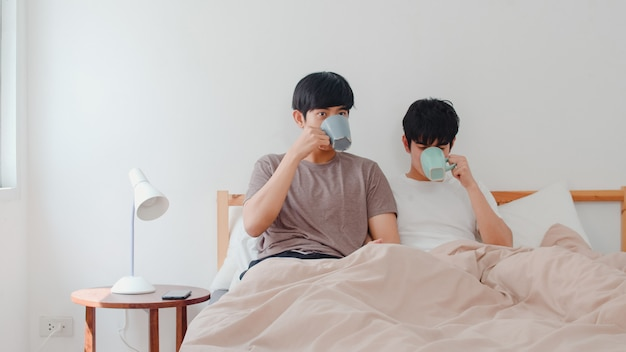 Asian gay men couple talking having a great time at modern home. young asia lover lgbtq+ male happy relax rest drink coffee after wake up while lying on bed in bedroom at house in the morning .