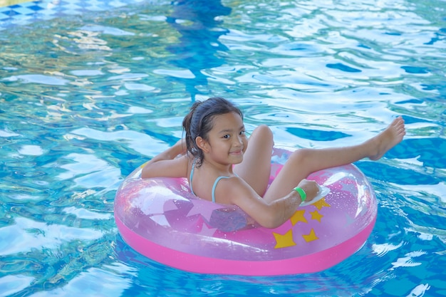 Asian girl (9-10) sitting on pink inflatable ring in swimming pool, summer vacation concept
