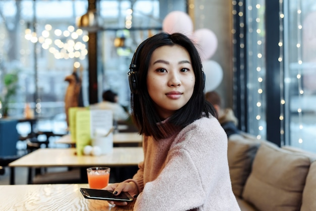 Asian girl alone in the city sits in a cafe and listens to music. enjoying music in a public place