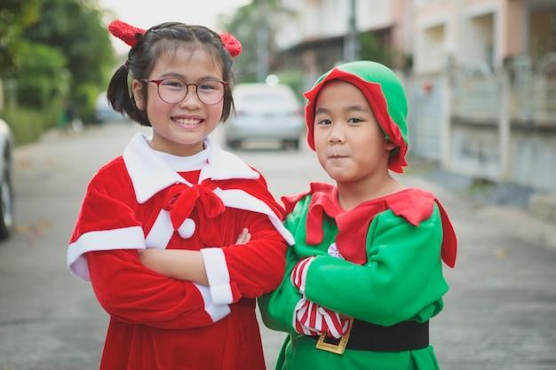 屋外で幸せと遊ぶサンタクロースのスーツを着ているアジアの女の子と男の子